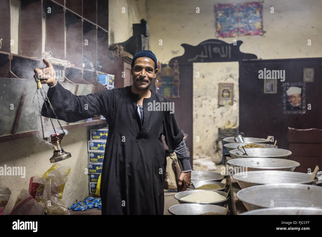 Man bestowing blessings upon a shop with an incense burner. - Stock Image
