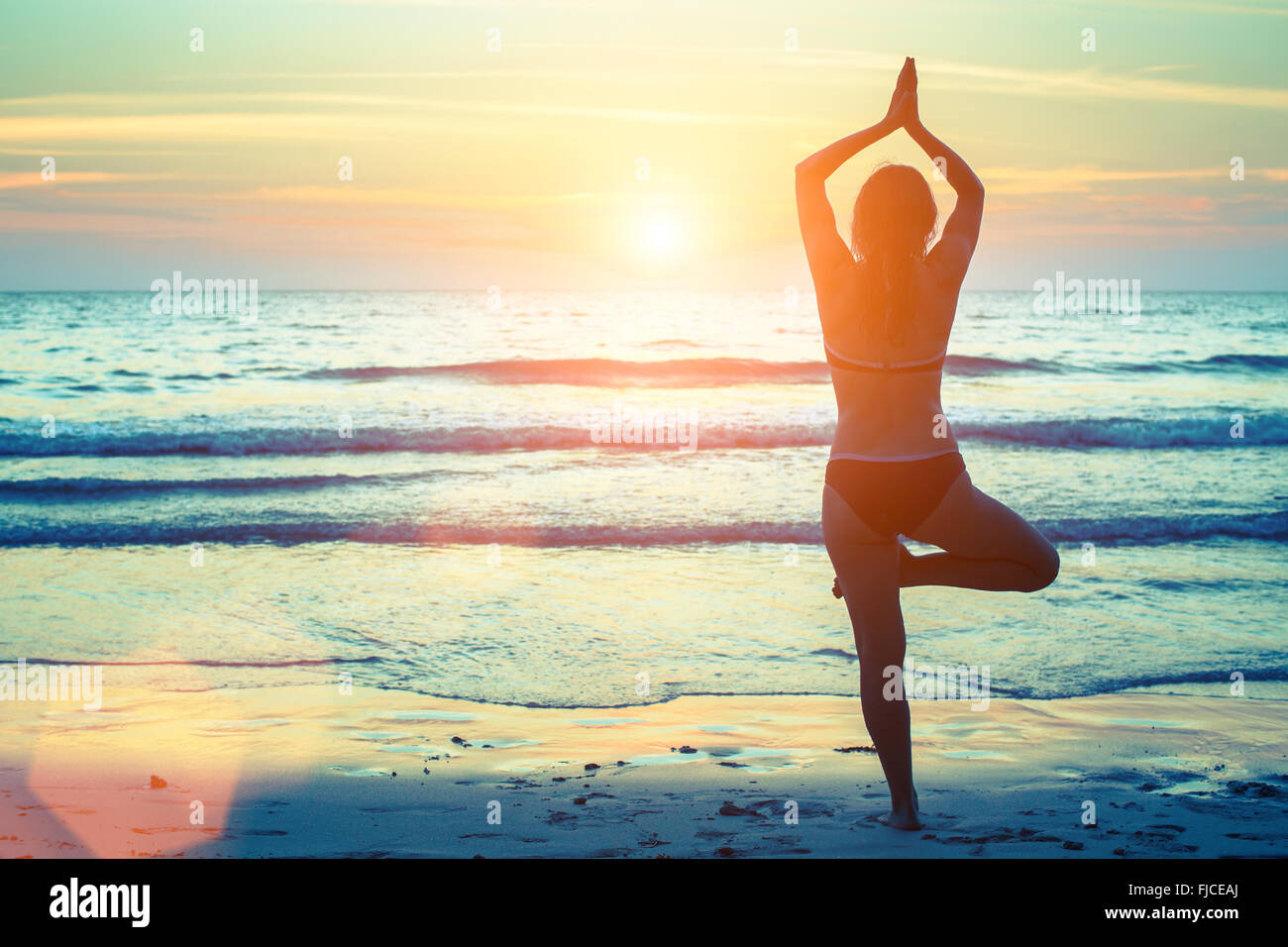 Silhouette of woman practicing yoga on the beach at sunset. - Stock Image
