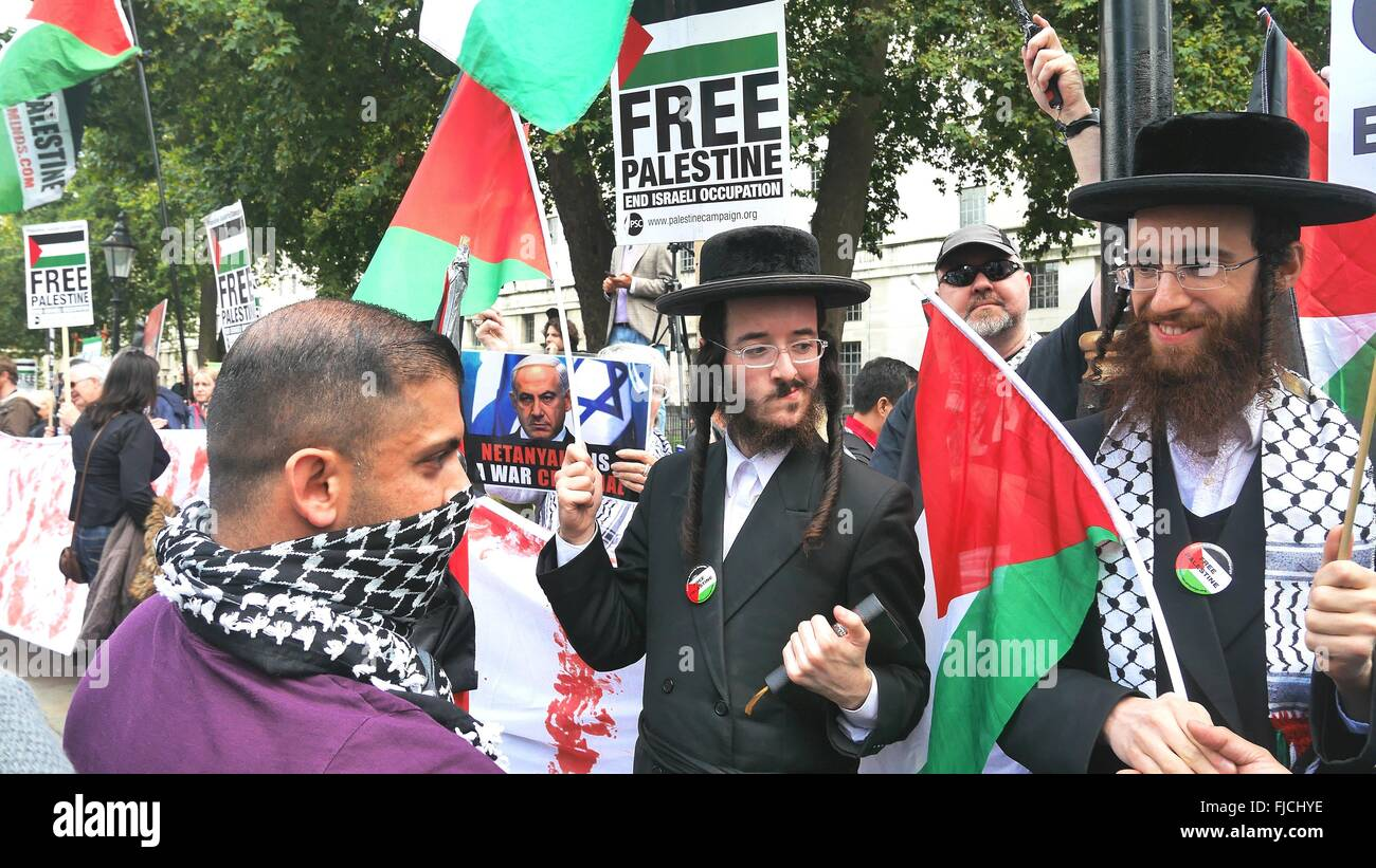 A pro Palestine supporter chats to anti-Zionist Orthodox Jews at a demonstration outside 10 Downing St, London. - Stock Image