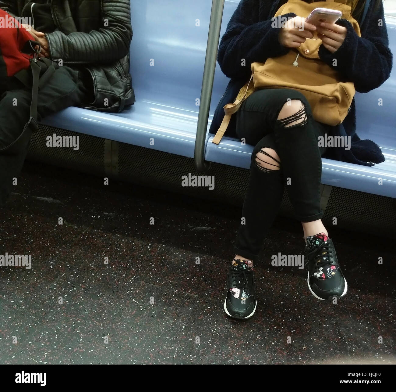 A teenager on the subway in New York texts while wearing her fashionably ripped jeans, seen on Sunday, February - Stock Image