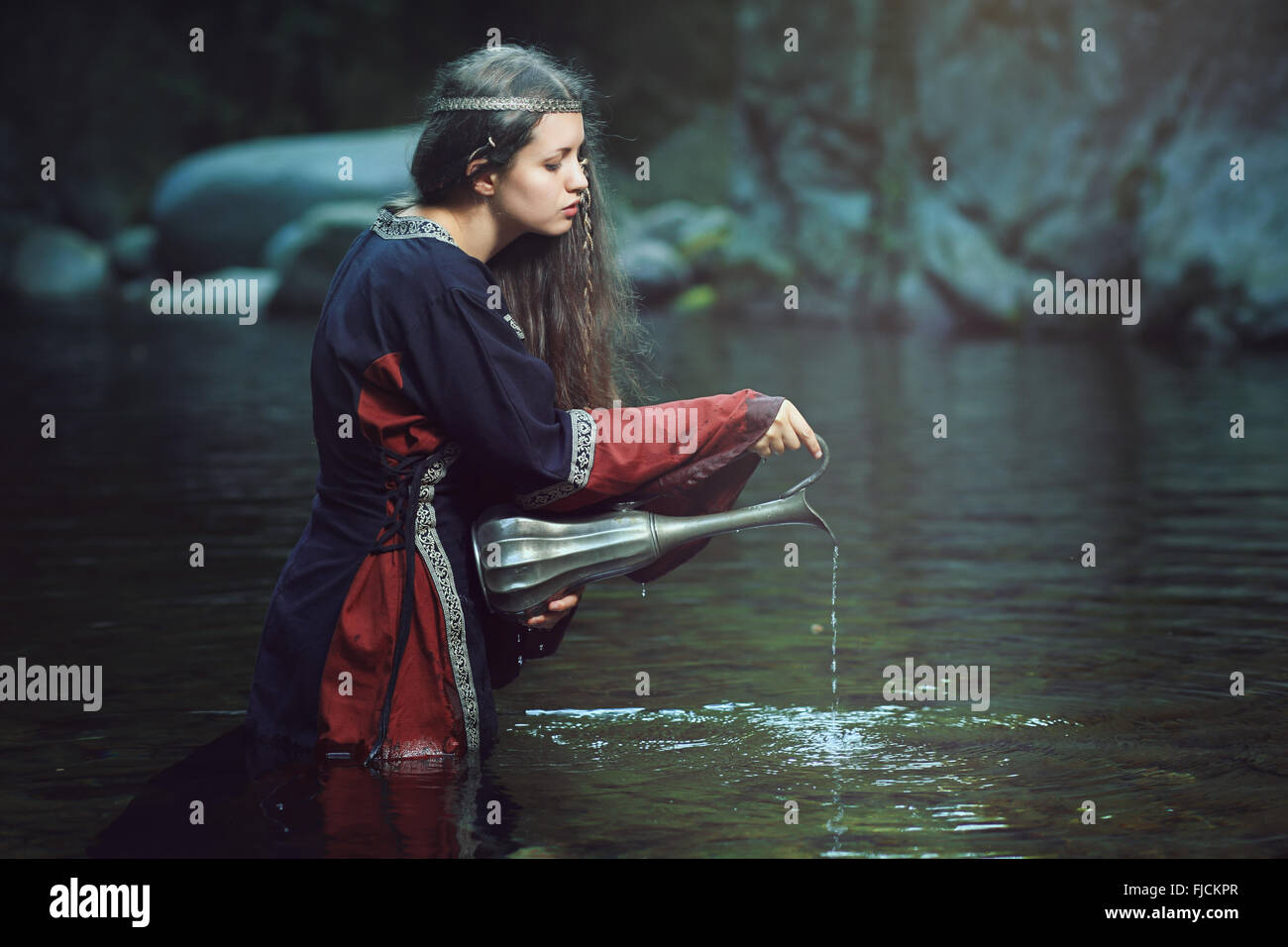 Ancient purification rite of a medieval woman in dark stream - Stock Image