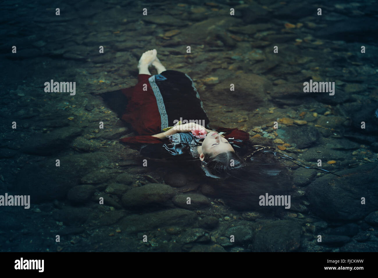 Beautiful floating woman in dark water . Ophelia conceptual - Stock Image
