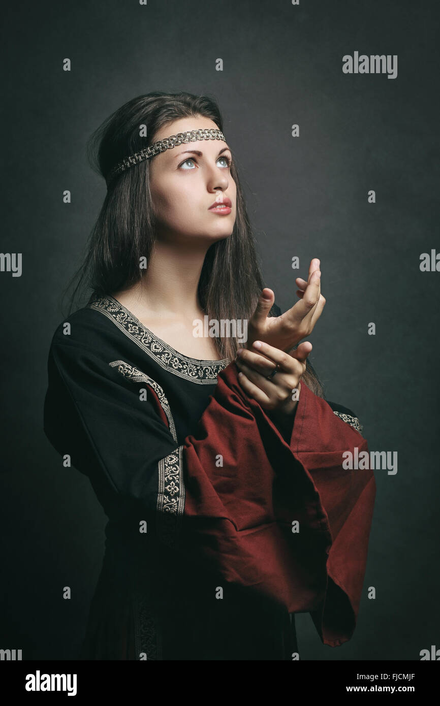 Beautiful woman in medieval dress praying with eyes to the sky. Historical and religion Stock Photo