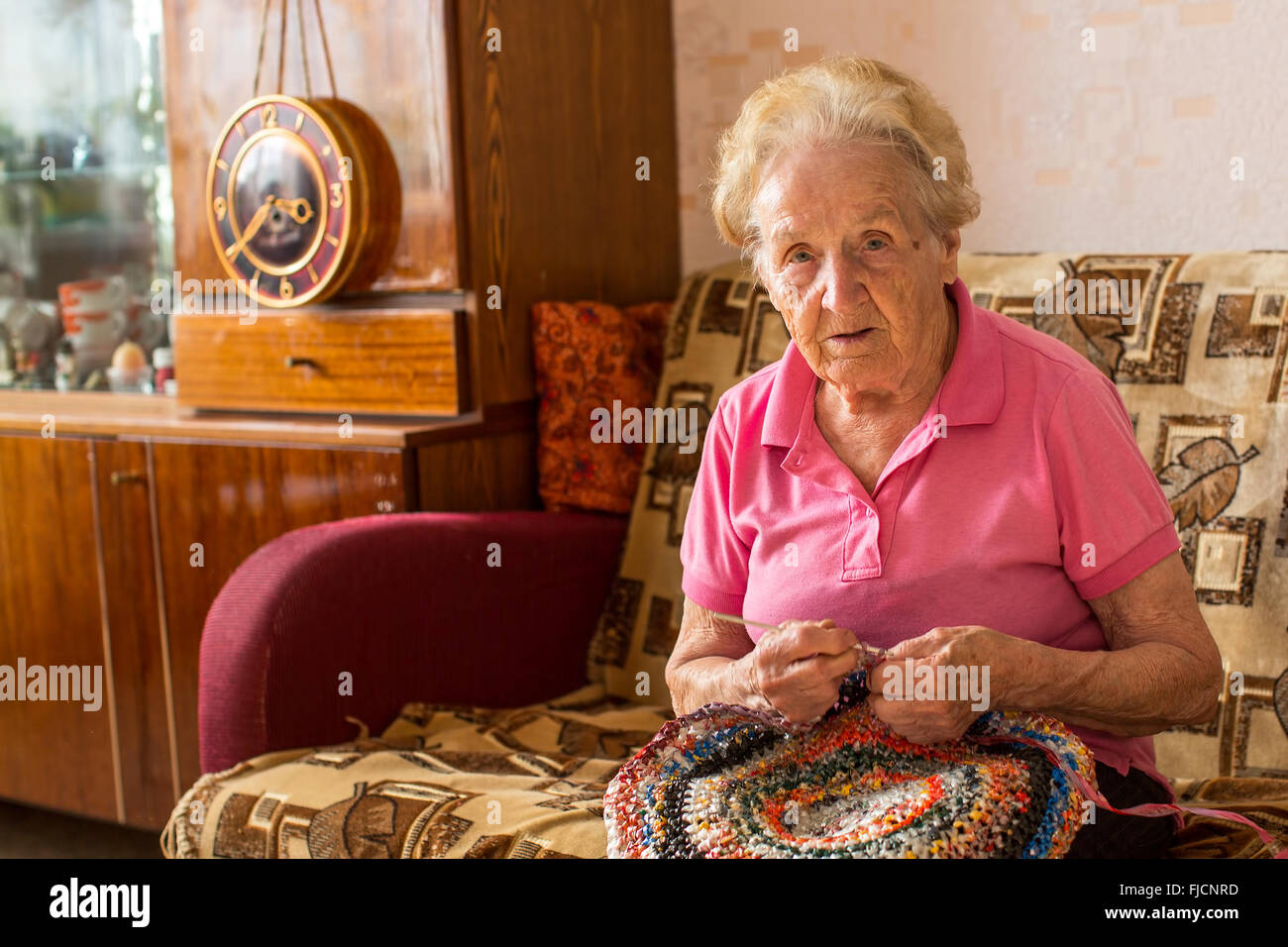 An elderly woman sitting in her room and knitting rug. - Stock Image