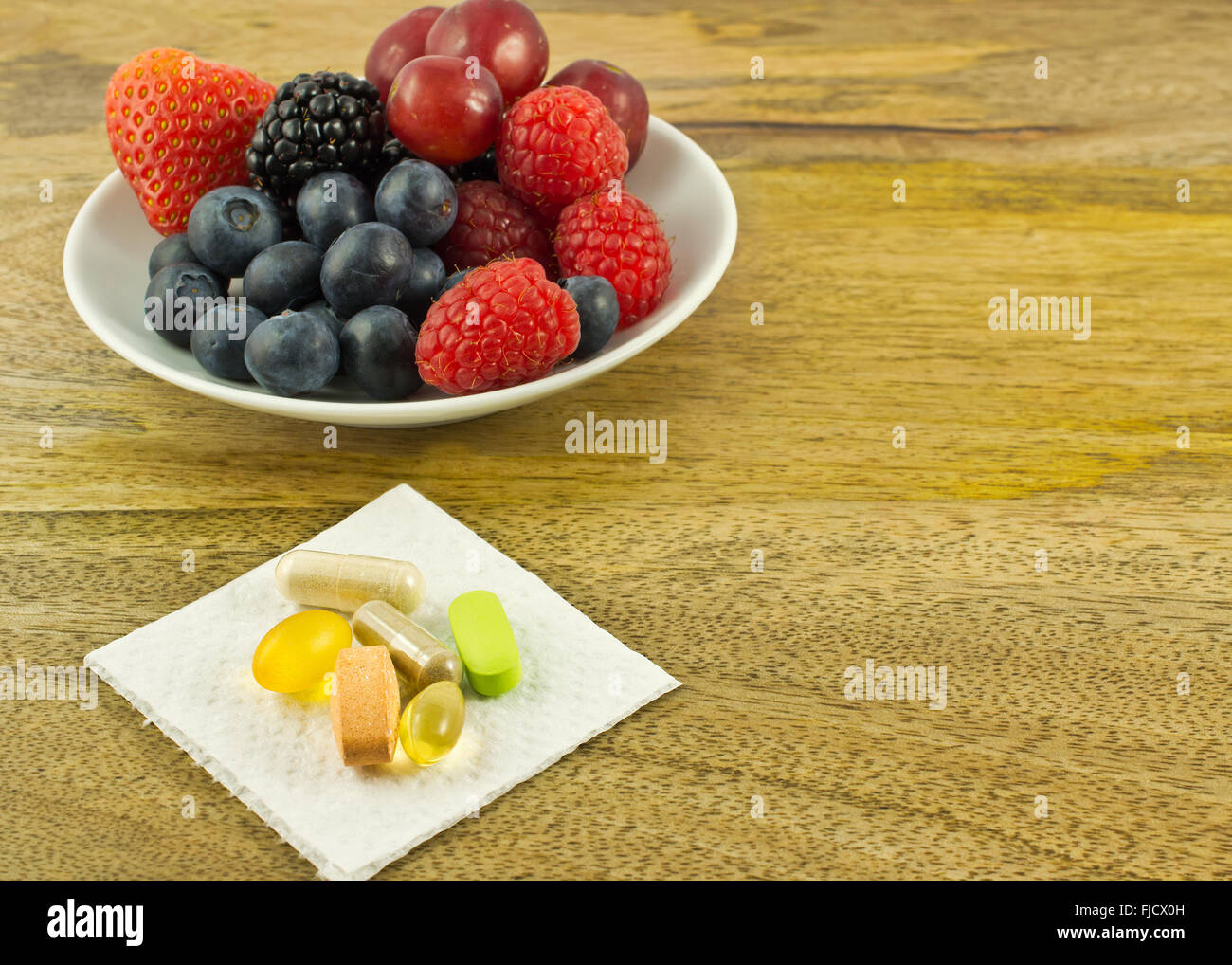 Berries and dietary supplements on wooden table - Stock Image