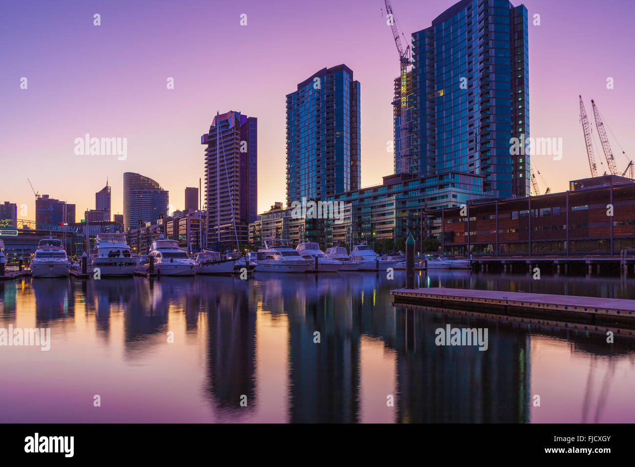 Docklands, Melbourne high rise residential buildings and moored yachts at dawn - Stock Image