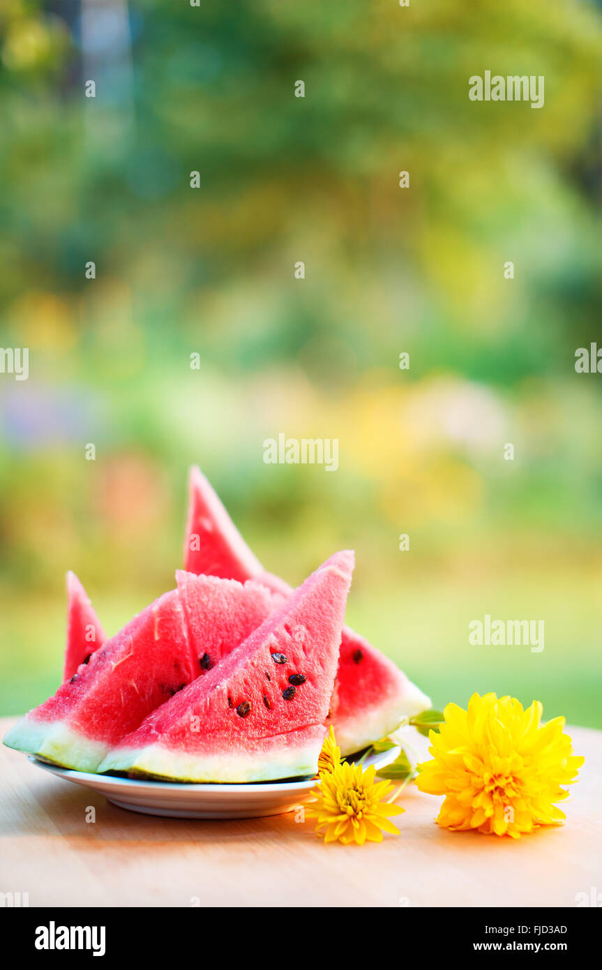 Ripe refreshing watermelon slices on a plate on wooden table and garden background. Refreshment for hot summer days - Stock Image