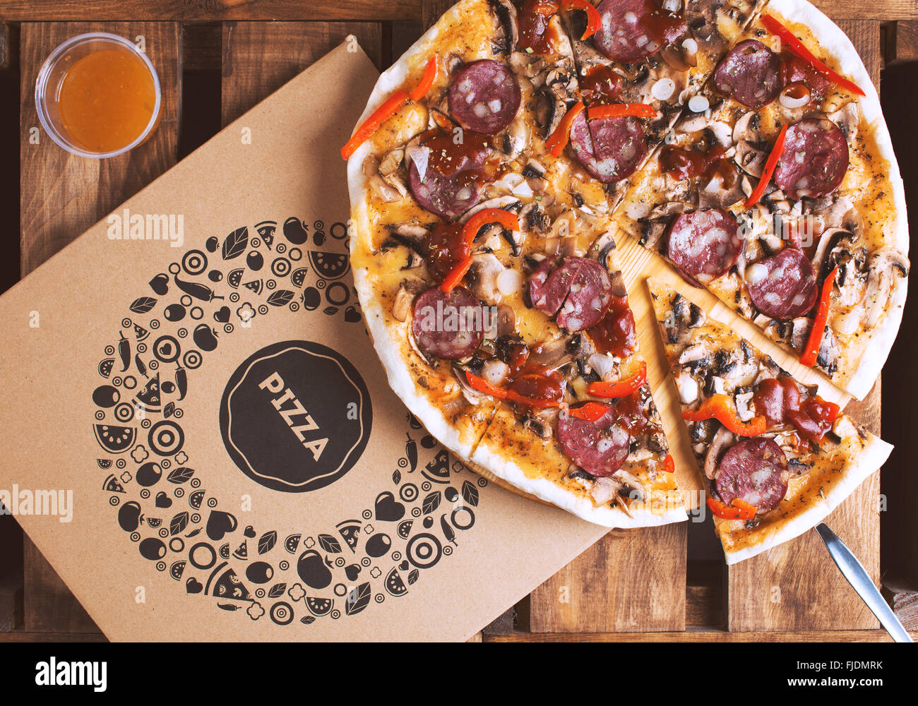 Flat lay shot of delicious italian pizza with meat and vegetables and cardboard delivery box. Pizza delivery service. - Stock Image