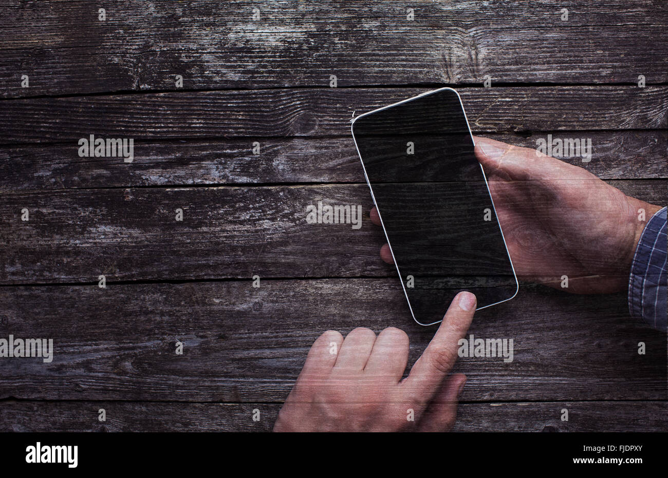 Male hands in shirt using smartphone with large blank touchscreen on dark rustic wood double exposure. With copy - Stock Image