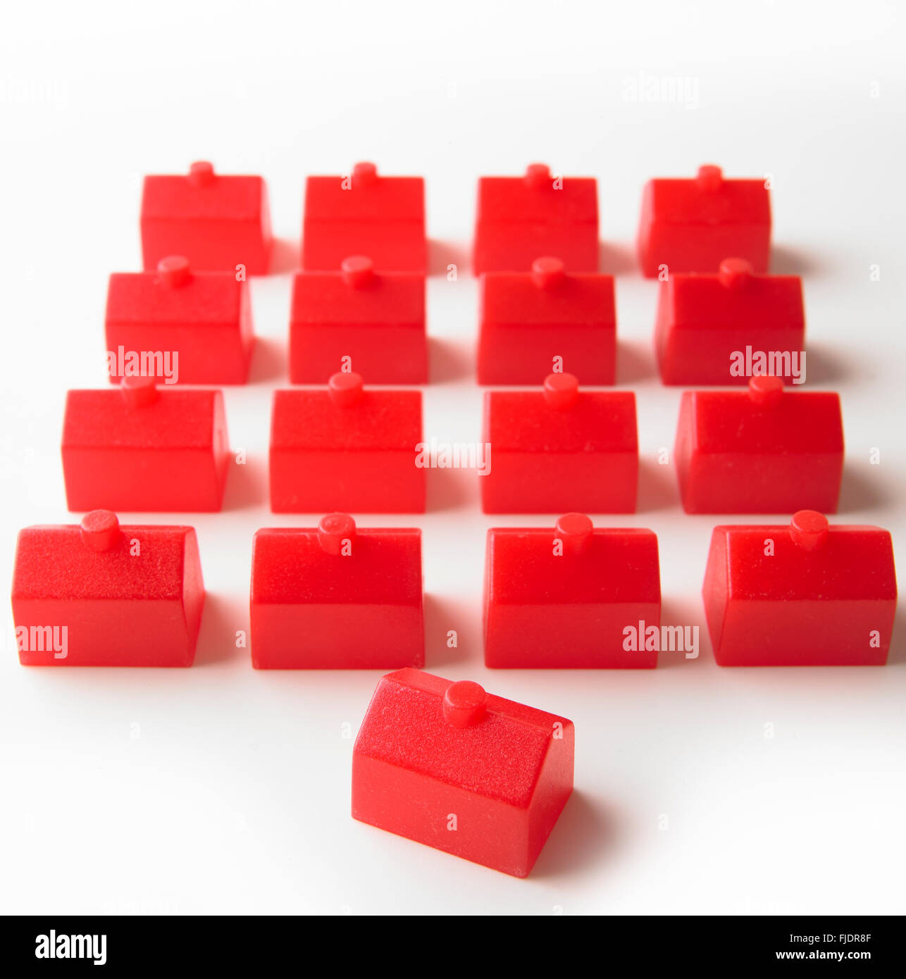 Identical red houses, one house angled in foreground - Stock Image