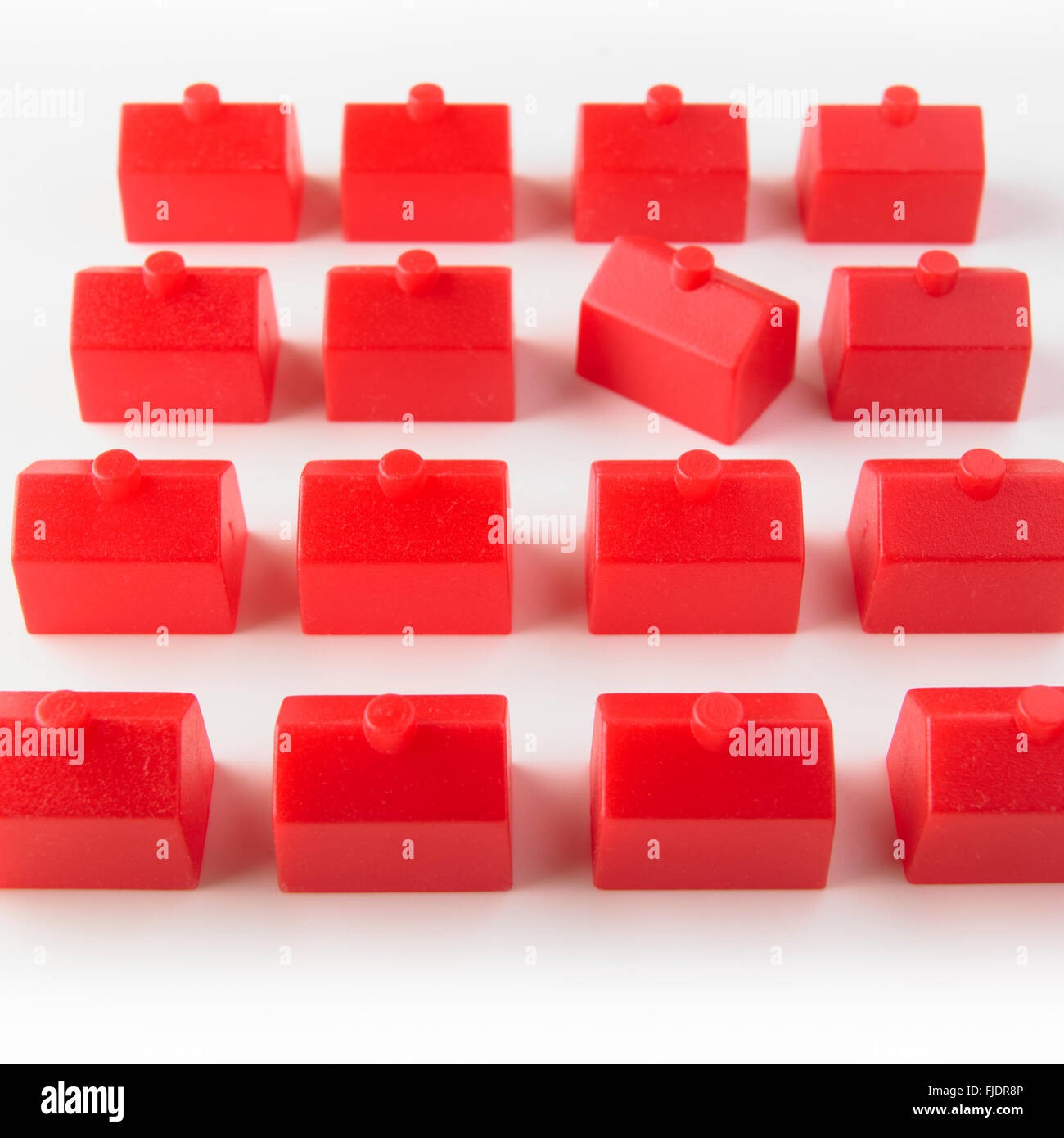 Identical red houses, one house angled - Stock Image