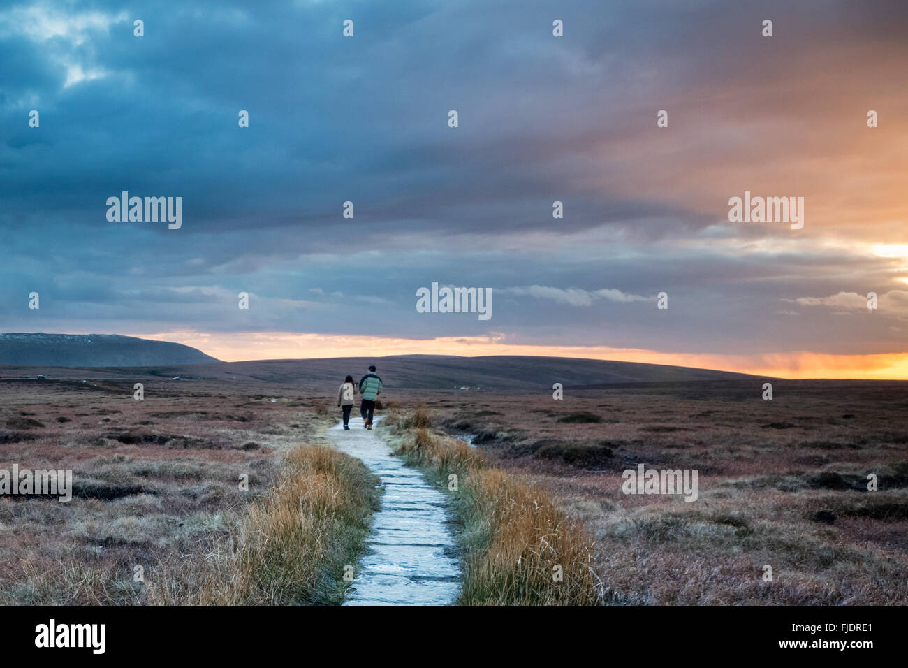 Two walkers enjoy a dramatic sunset whilst walking on the Pennine Way from Bleaklow to Kinder Scout in the Peak - Stock Image