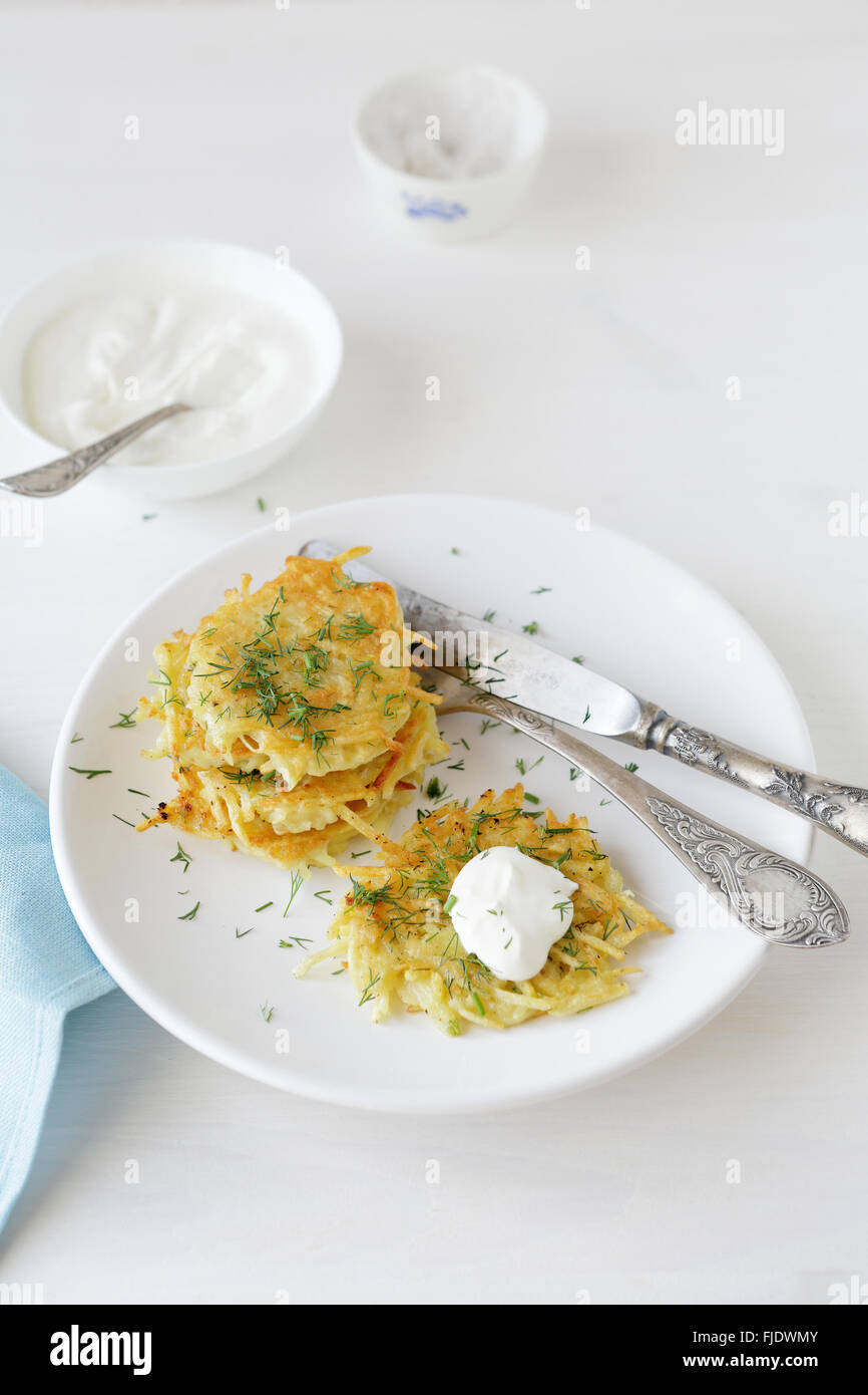 potato pancake with dill on white plate - Stock Image