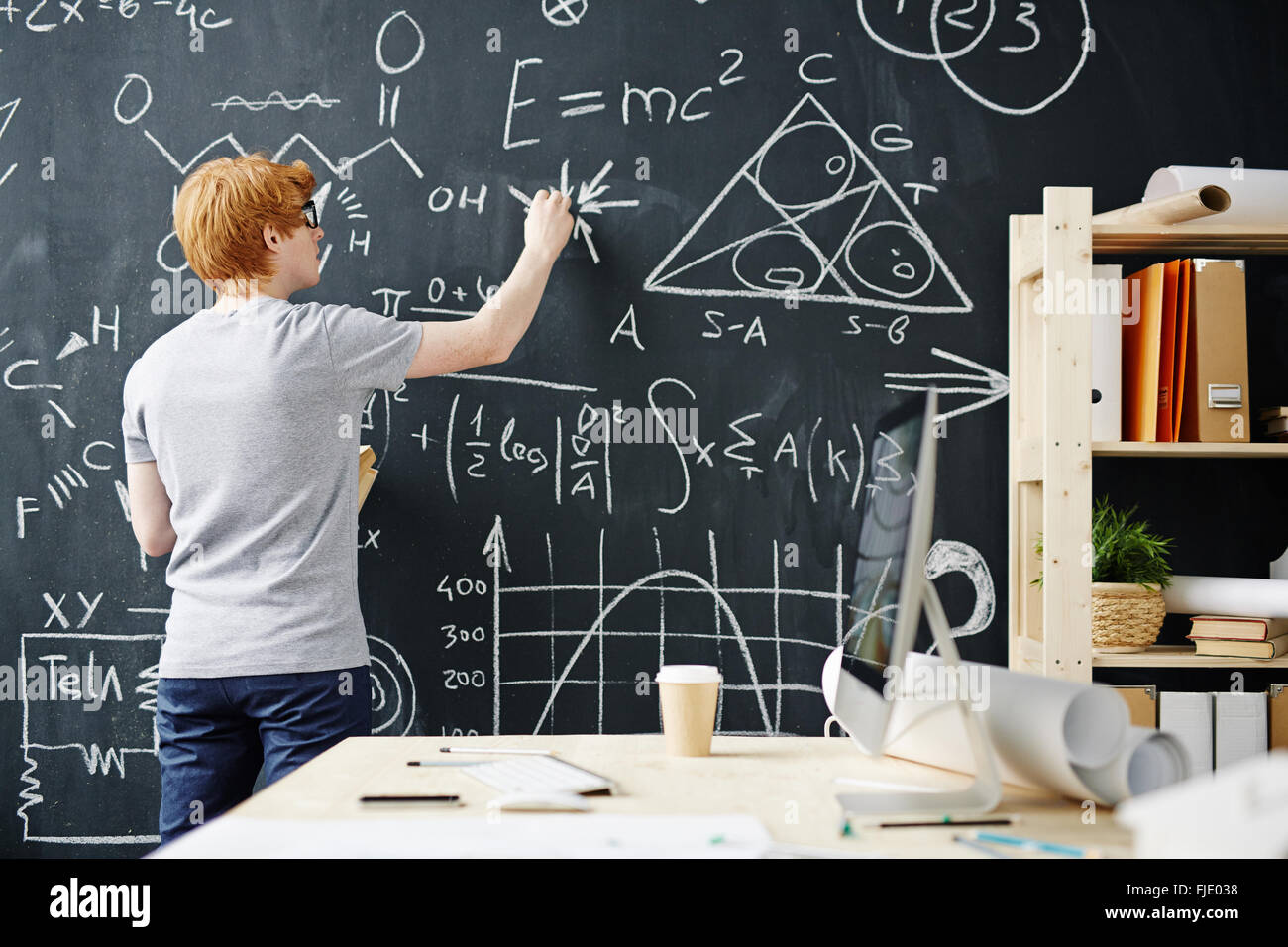 College student writing on the chalkboard during a math class Stock ...