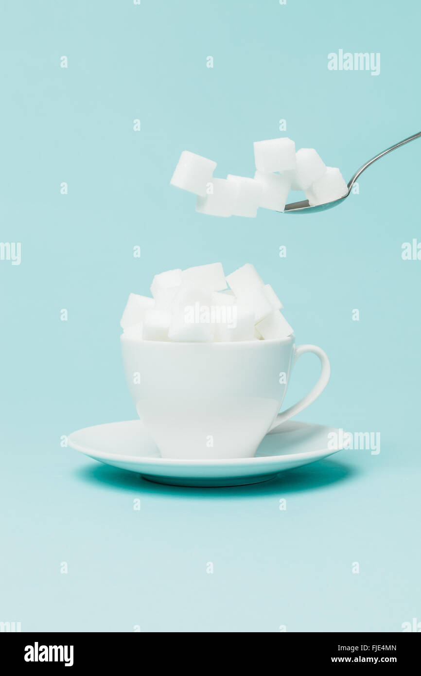 Adding an excessive amount of sugar in a tea cup. - Stock Image