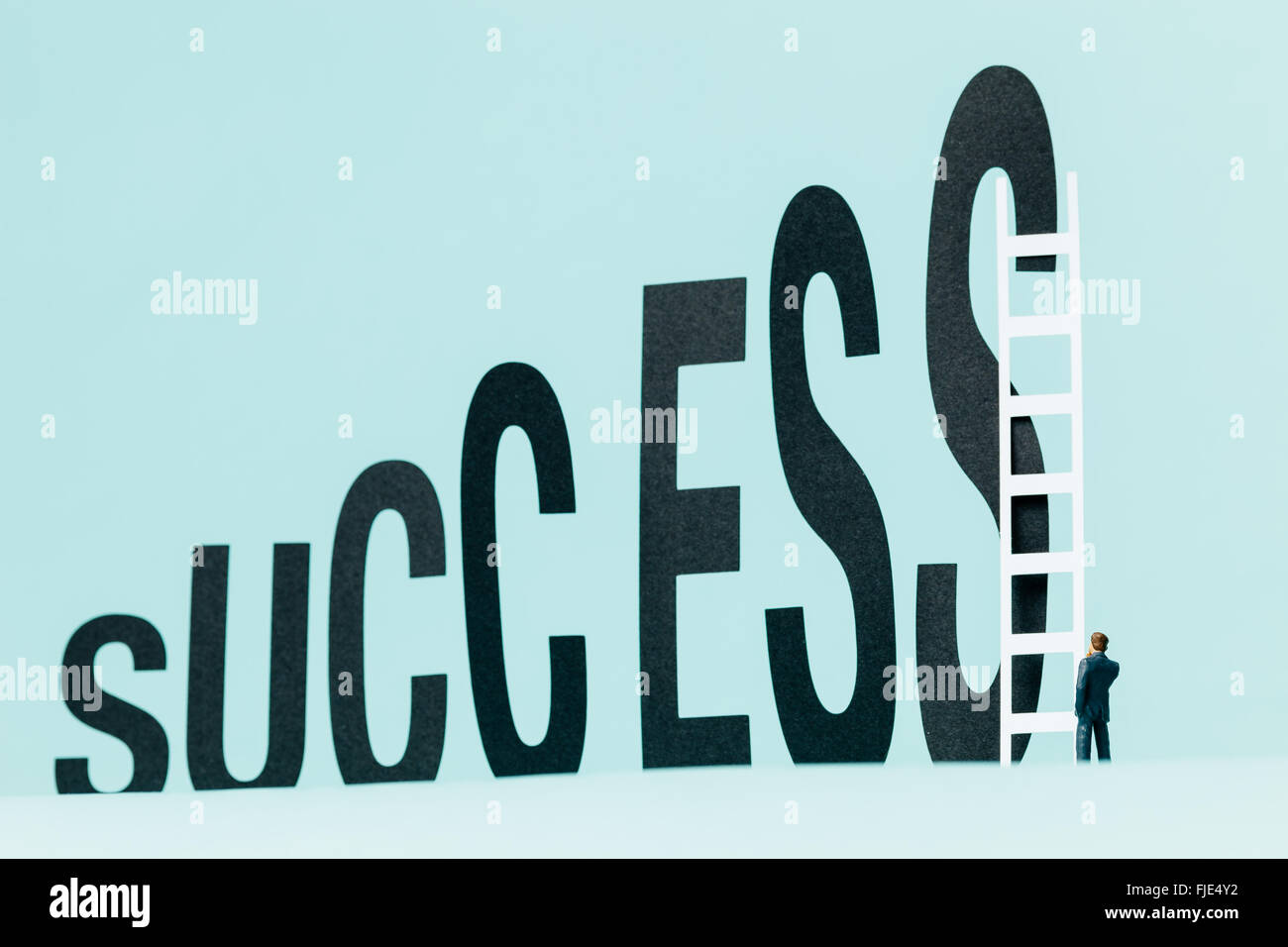 Miniature businessman observing a ladder ready to get a promotion and be successful. - Stock Image