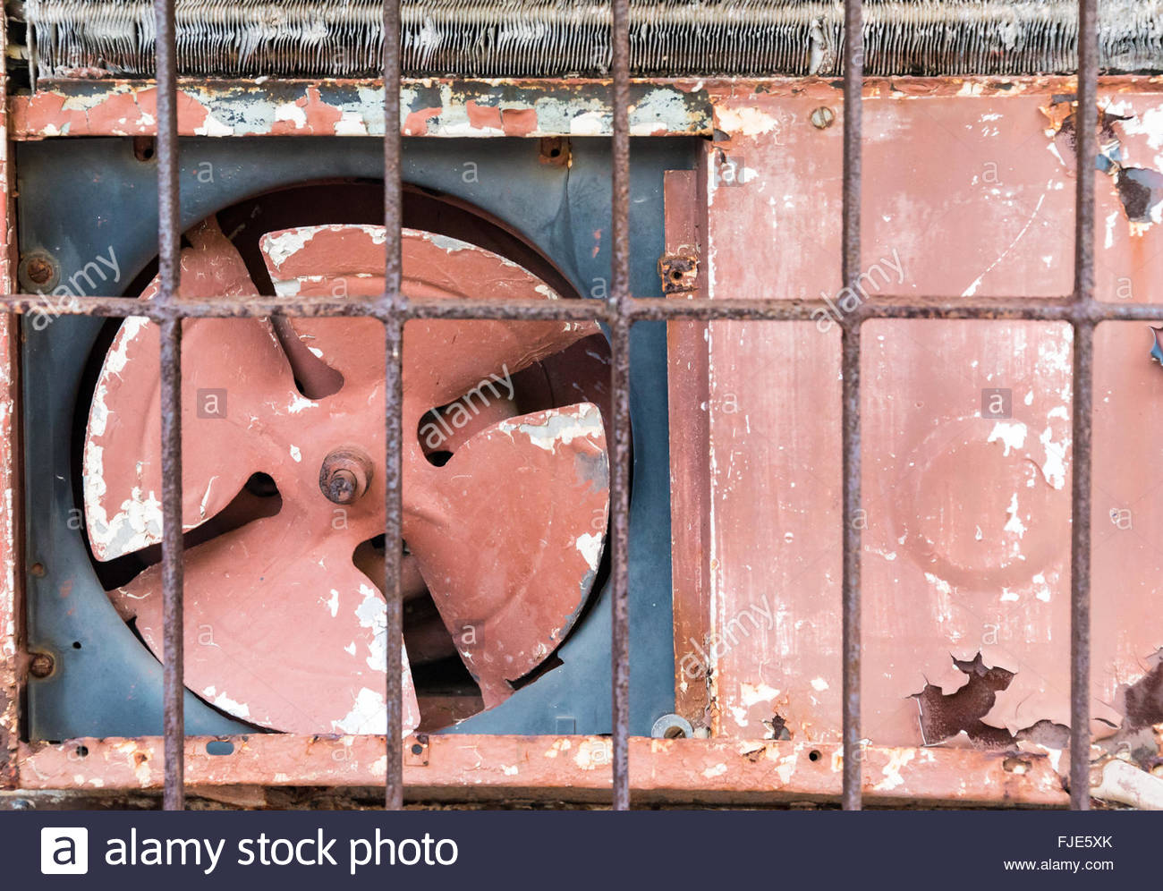 Oudoor side of an old rusty red air conditioner. Cubans manage to get the most incredible pieces of equipment in - Stock Image