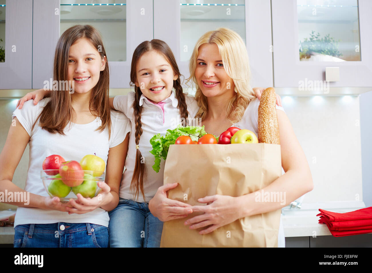 Young family in the kitchen with a bag of groceries shopping - Stock Image