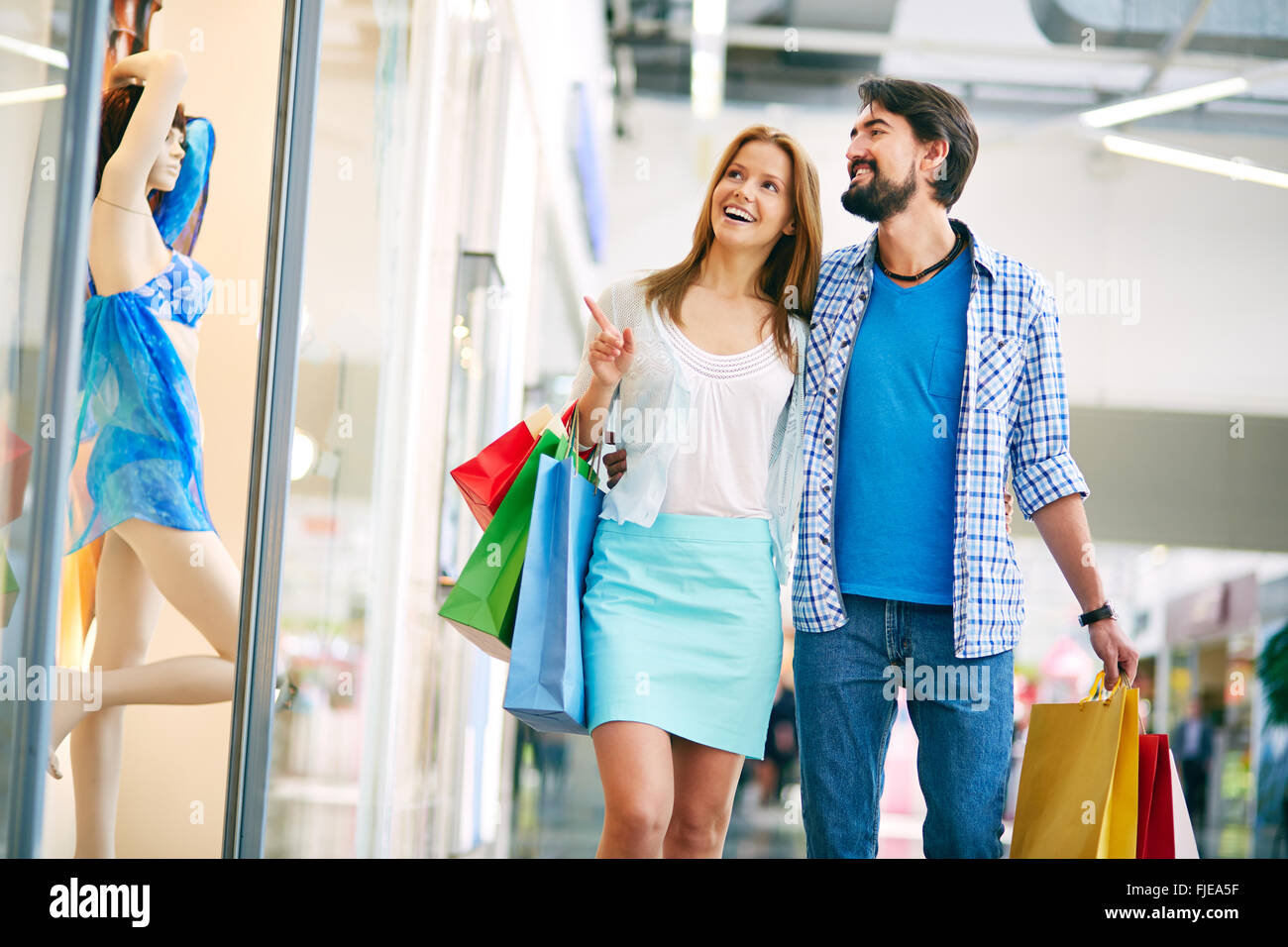 Woman showing something to her boyfriend in the shopping mall Stock Photo