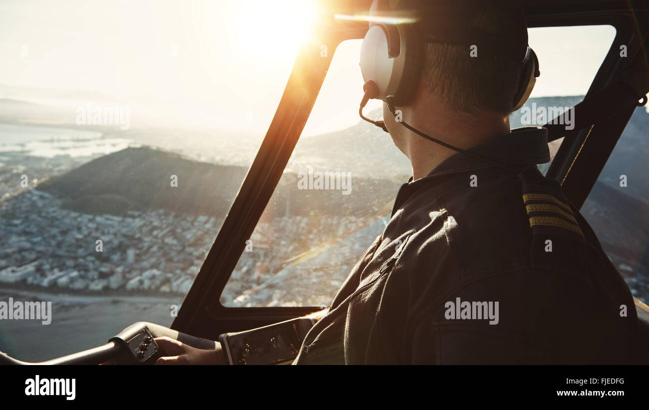Close up of a male pilot flying a helicopter and looking outside the window with sun flare entering the cockpit. - Stock Image