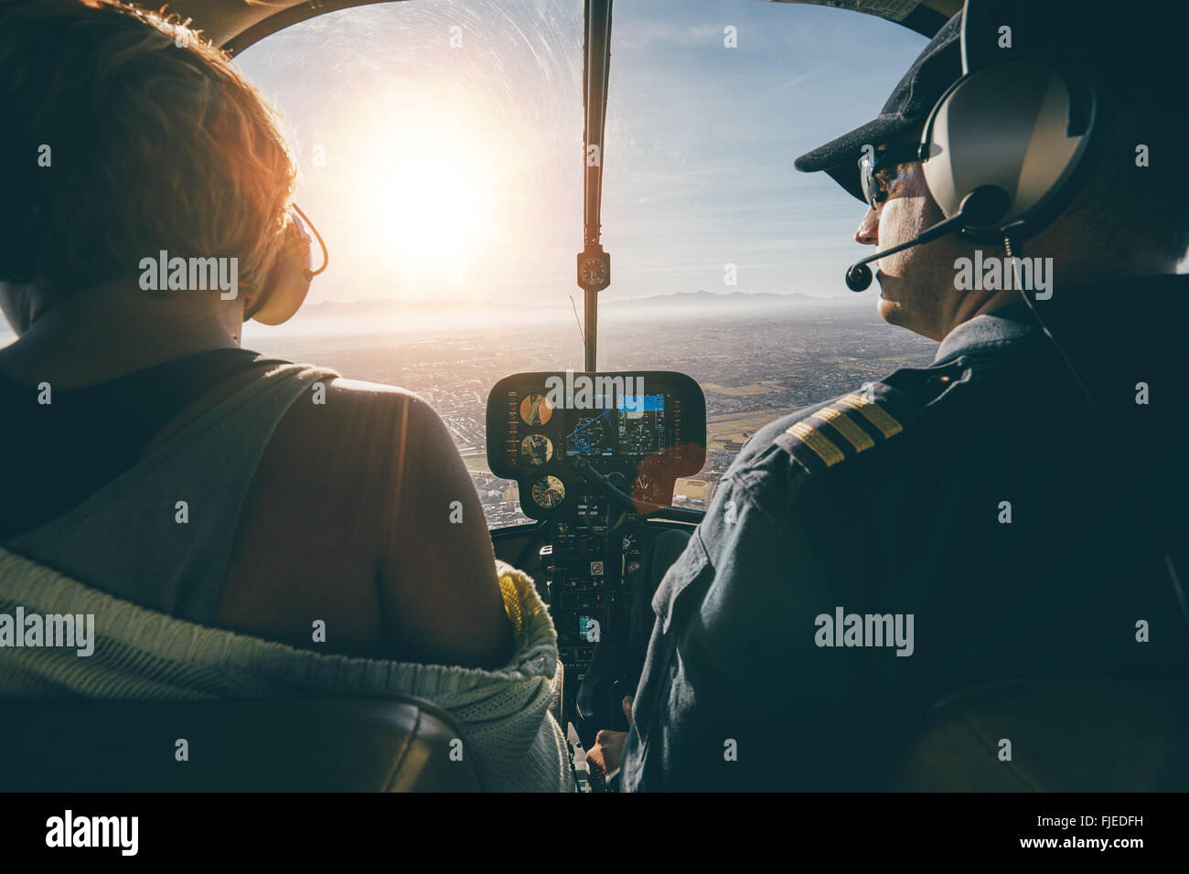 Rear view of male and female pilots flying a helicopter on sunny day. Man flying a helicopter with his copilot looking - Stock Image