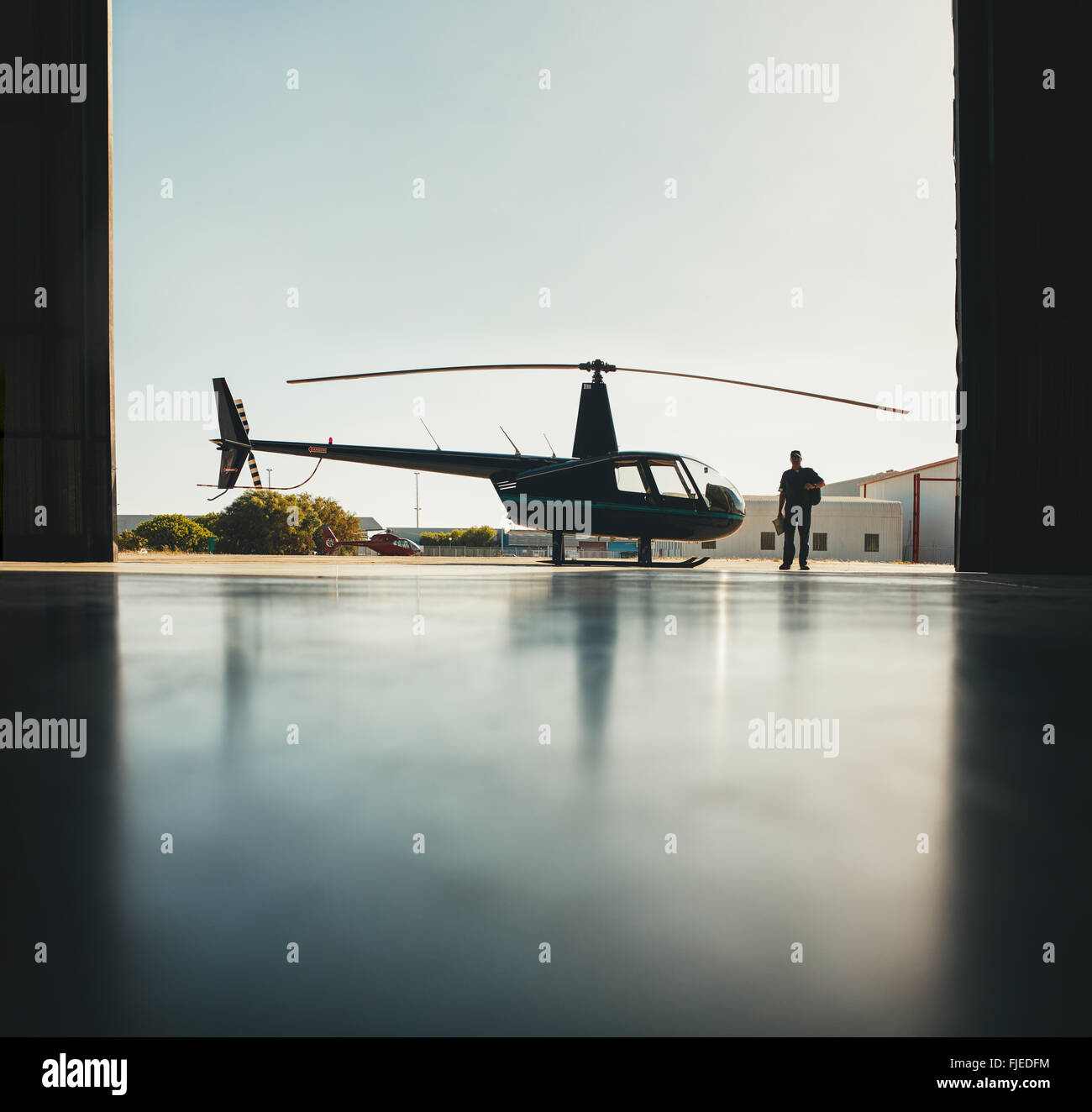 Silhouette of helicopter with a pilot walking in the airplane hangar after the flight. - Stock Image