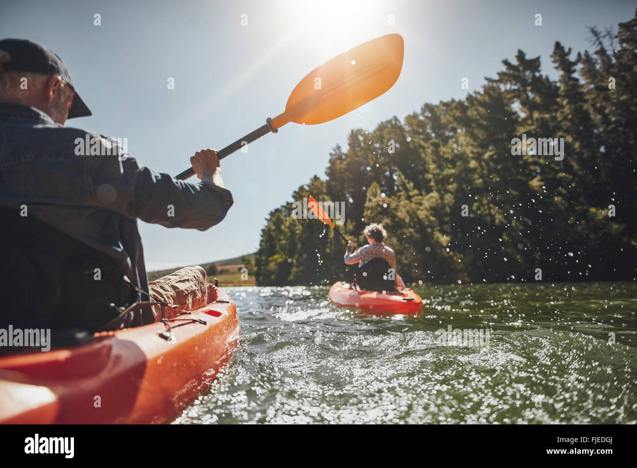 Outdoor shot of senior man canoeing in the lake with woman in background on a summer day. Man and woman in two different Stock Photo
