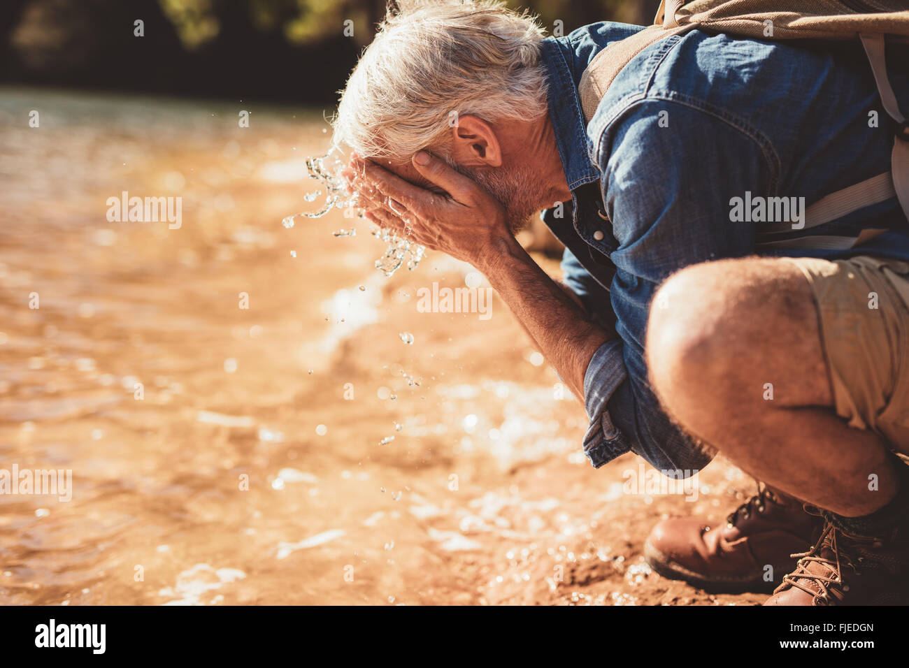 Side portrait of a mature man washing his face in the lake during a hike. Senior man with backpack sitting at the - Stock Image