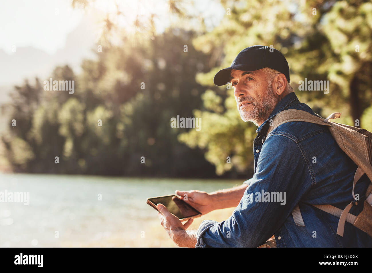 Portrait of senior man sitting near a lake with backpack and digital tablet. Mature male hiker sitting at a lake Stock Photo
