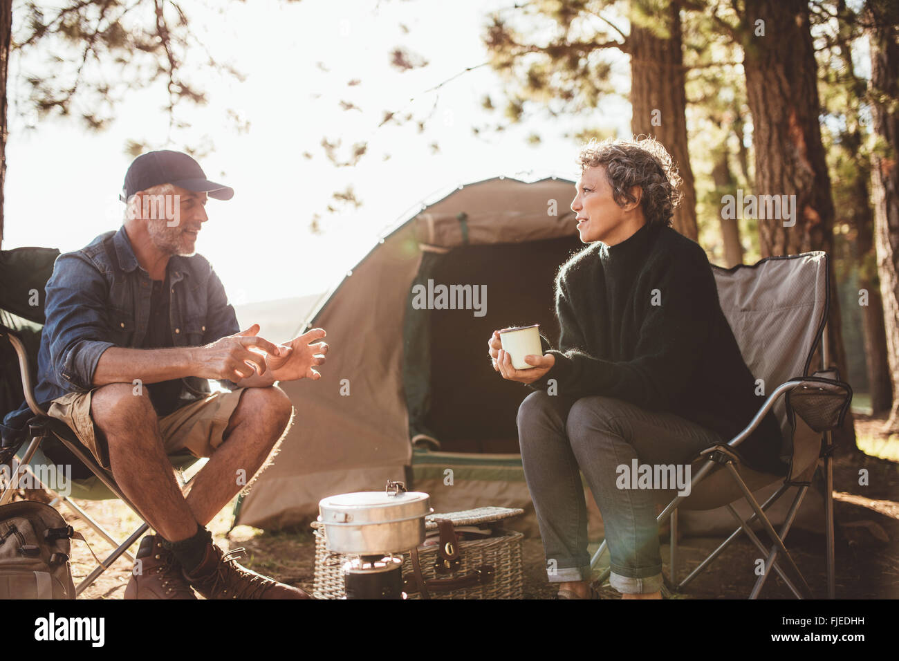 Mature man and woman sitting and talking at a campsite. Senior couple sitting in chairs outside the tent on a summer - Stock Image