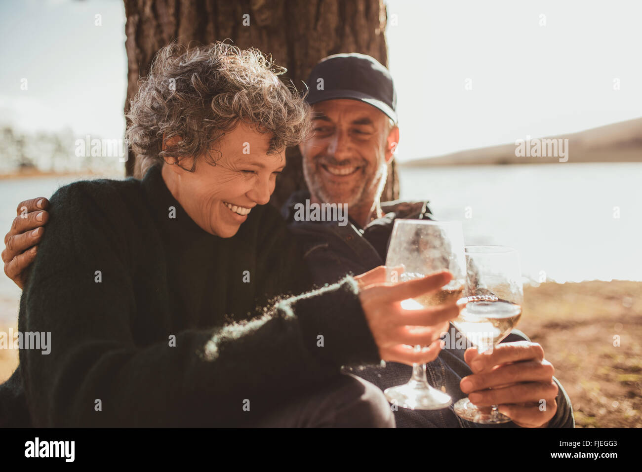 Portrait of relaxed mature couple having a glass of wine at campsite. Senior man and woman toasting wine at on summer - Stock Image