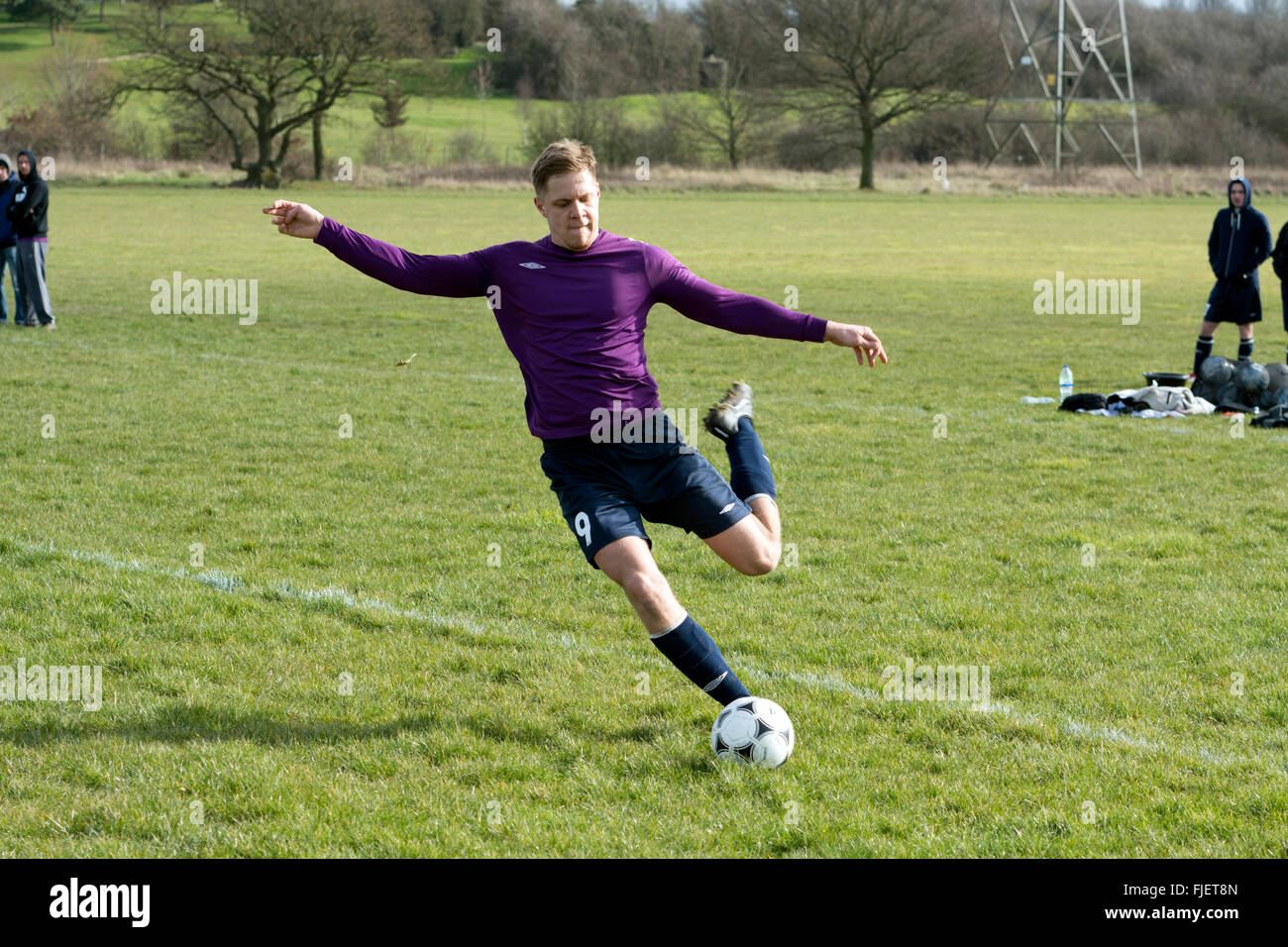 Sunday League football, player kicking ball - Stock Image