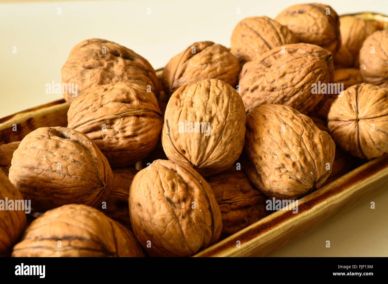 Walnuts in shells in a porcelain container. - Stock Image