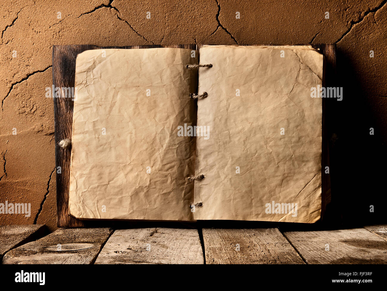 Opened old book on table near clay wall - Stock Image