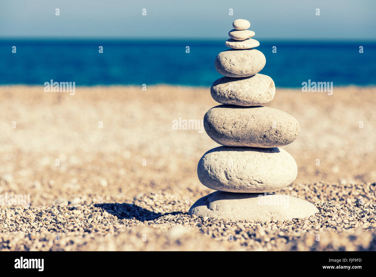 Stones balance, vintage retro instagram like hierarchy stack over blue sea background. Spa or well-being, freedom - Stock Image