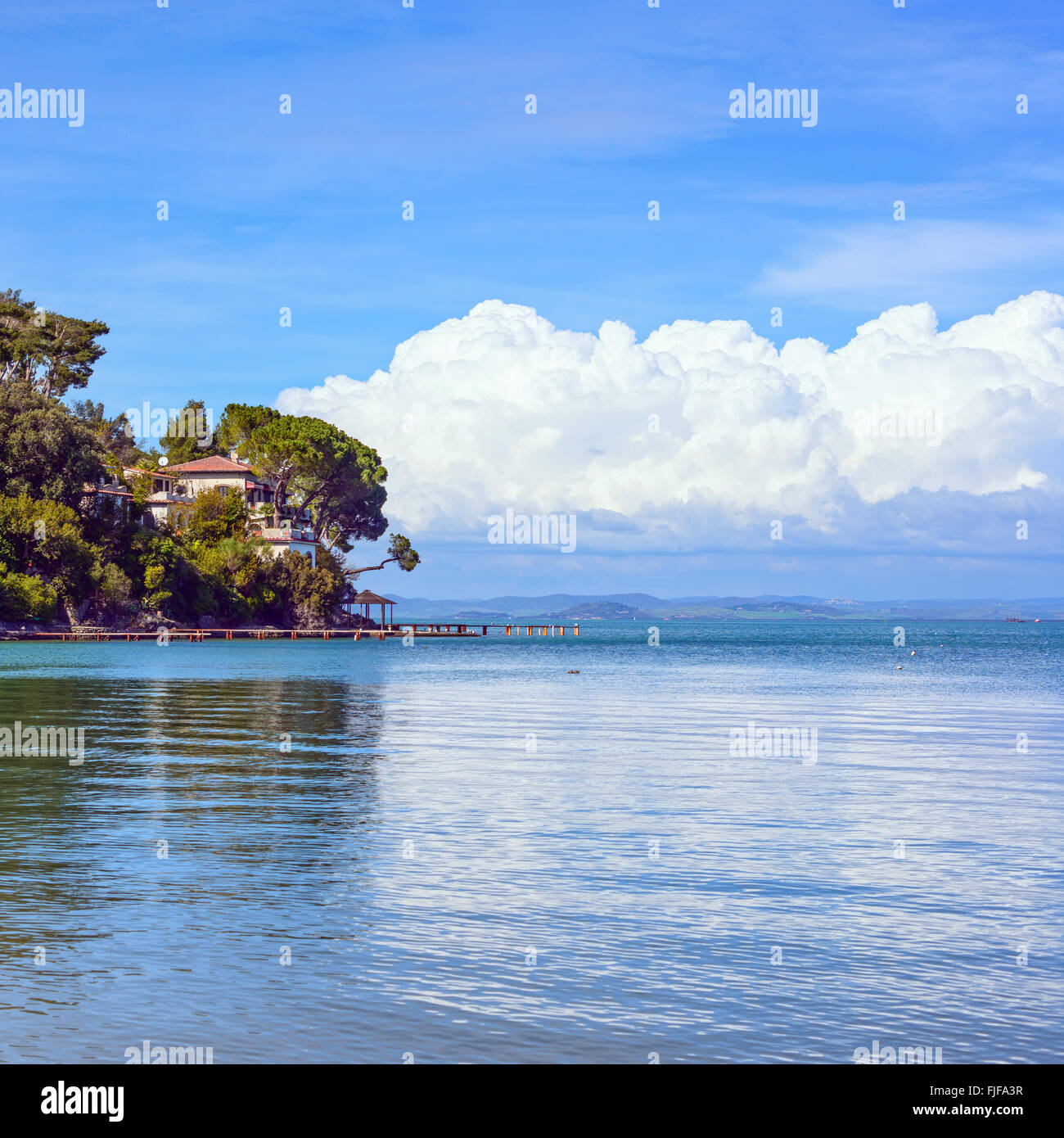 Headland, trees, and pier or jetty on a blue ocean and cloudy sky. Bay beach in Monte Argentario, Porto Santo Stefano, - Stock Image