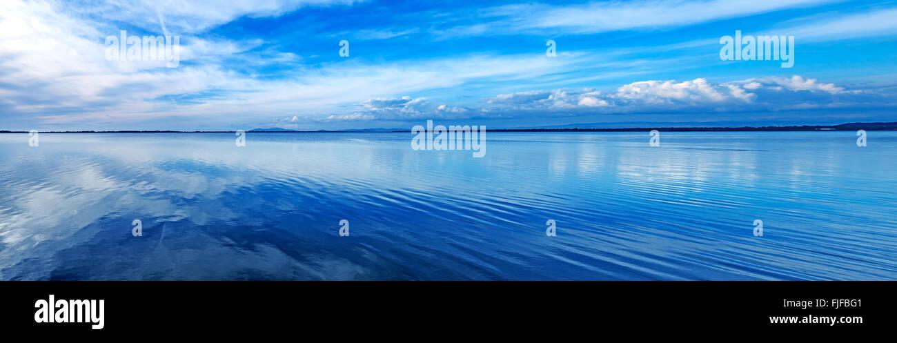 Sunset blue panoramic landscape. Orbetello lagoon with reflection, Argentario, Tuscany, Italy. - Stock Image