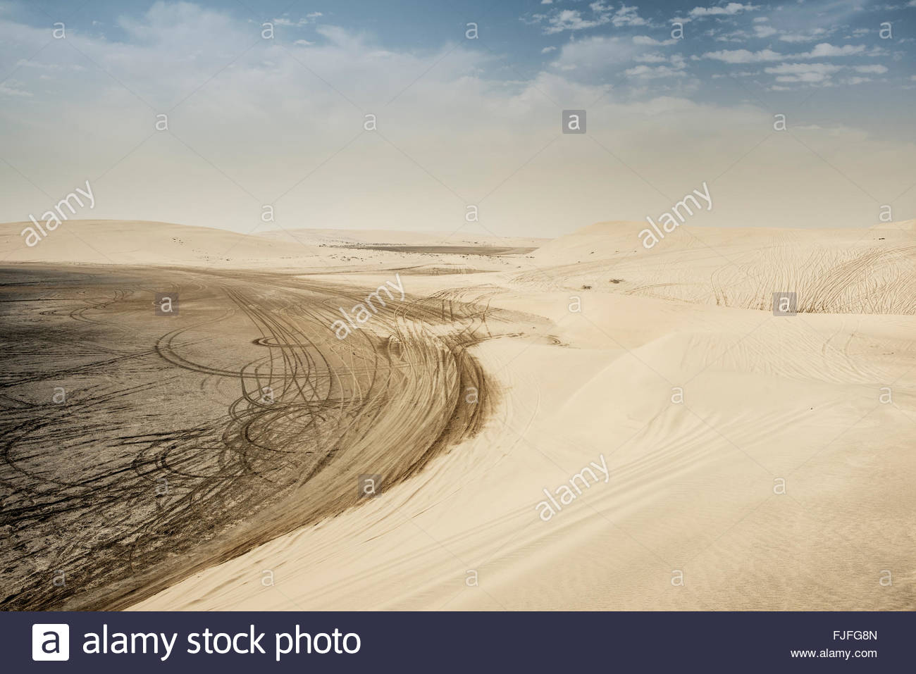 Quad bike tyre tracks in the dunes of the Inland Sea (Khor al Adaid) in southern Qatar - Stock Image