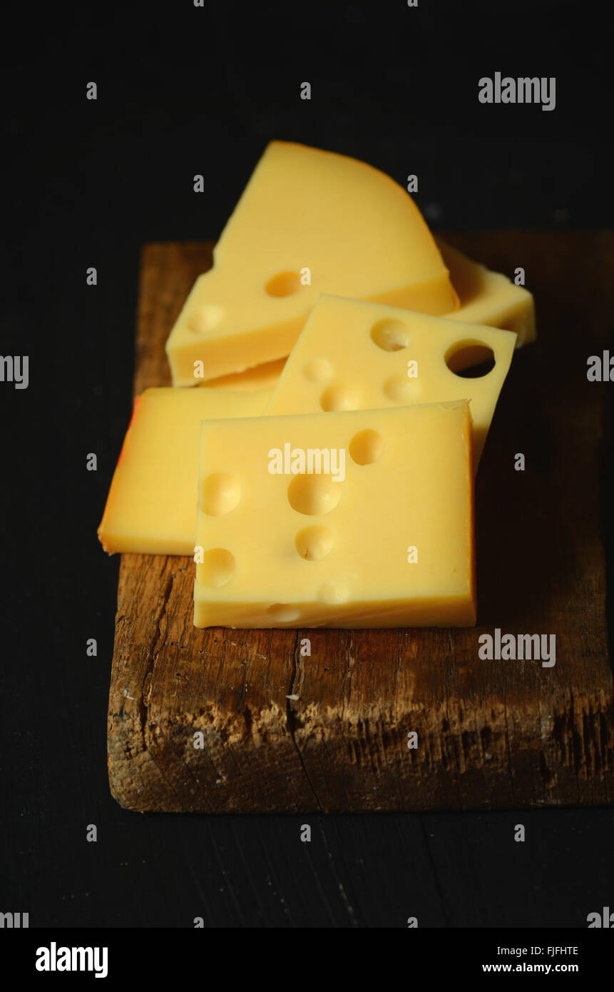 Pieces and slices of swiss cheese, close up image - Stock Image