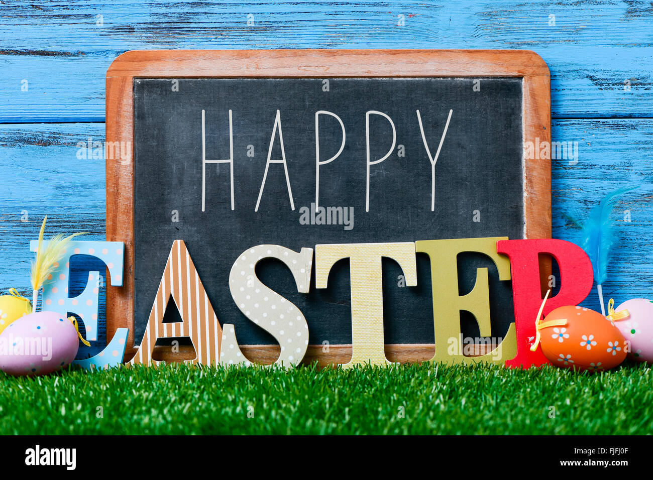 some decorated eggs on the grass, and the text happy written in a chalkboard and three dimensional letters forming - Stock Image