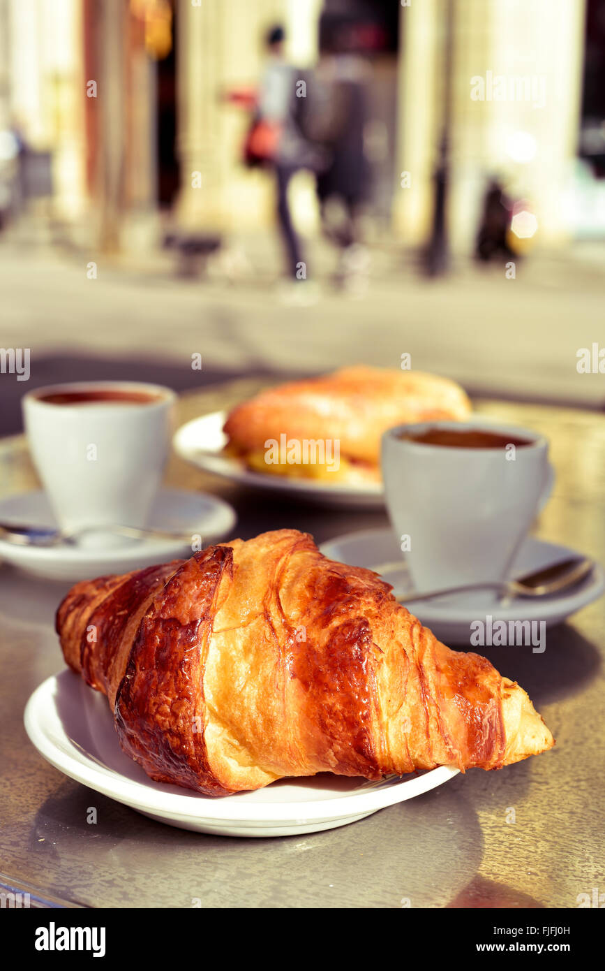 closeup of a table in the terrace of a cafe set for breakfast, with some cups of coffee, a croissant and a spanish Stock Photo