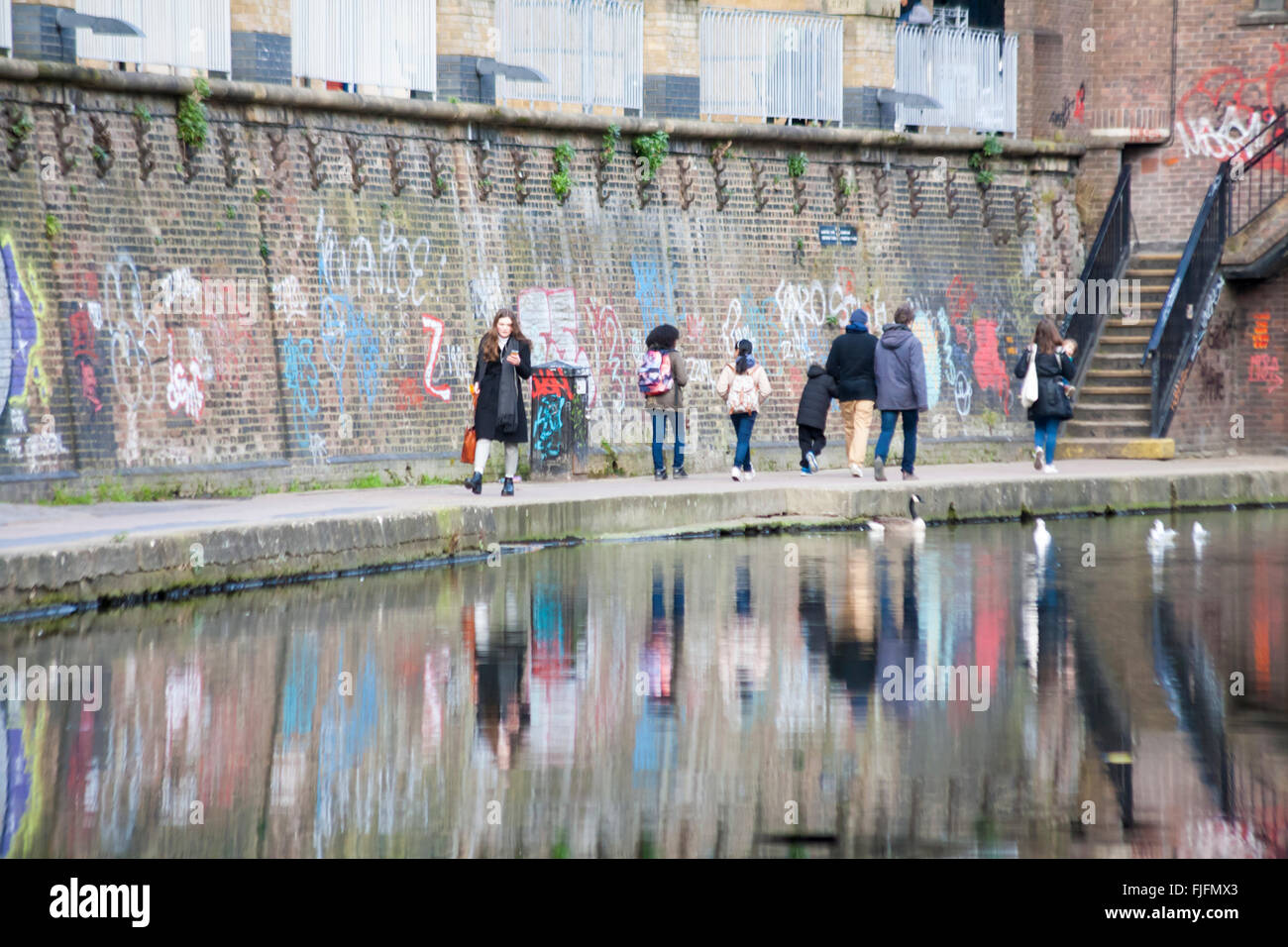 People walking along Regents Canal towpath reflected in water passing graffiti on wall, London in February - Stock Image