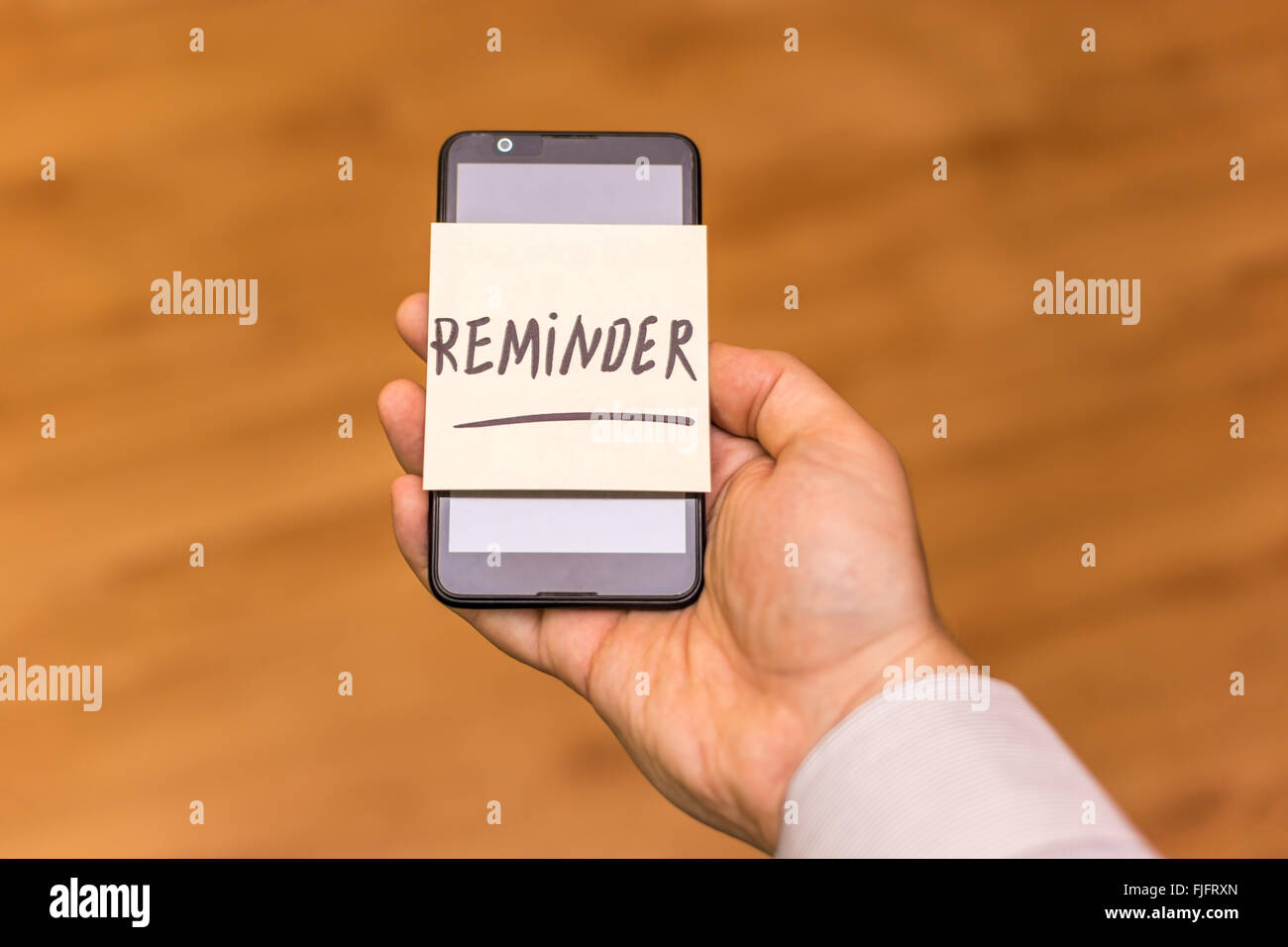 Human hand holding a smartphone with yellow note sticked on it. The word reminder is written on the note. Stock Photo