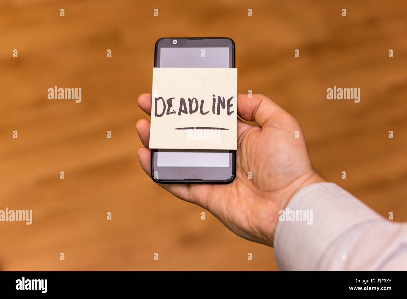 Human hand holding a smartphone with yellow note sticked on it. The word deadliner is written on the note. Stock Photo