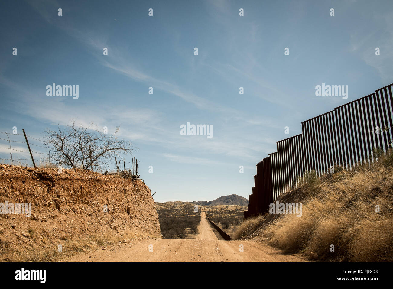 A border patrol road winds along the line of the U.S. Mexico border in southern Arizona - Stock Image