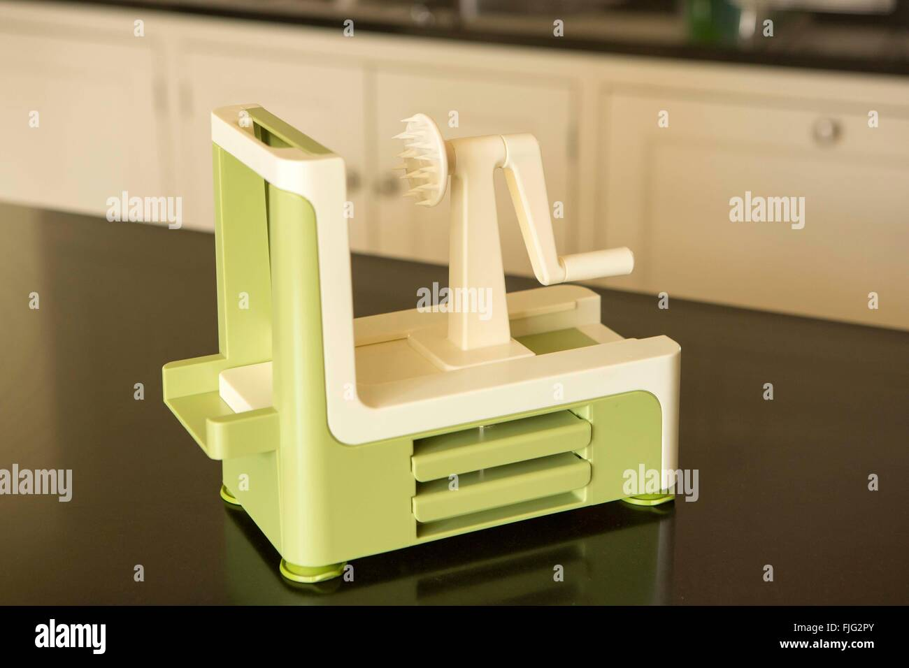 A kitchen gadget that is used to cut raw vegetables into long spirals resembling spaghetti, also known as a spiralizer - Stock Image