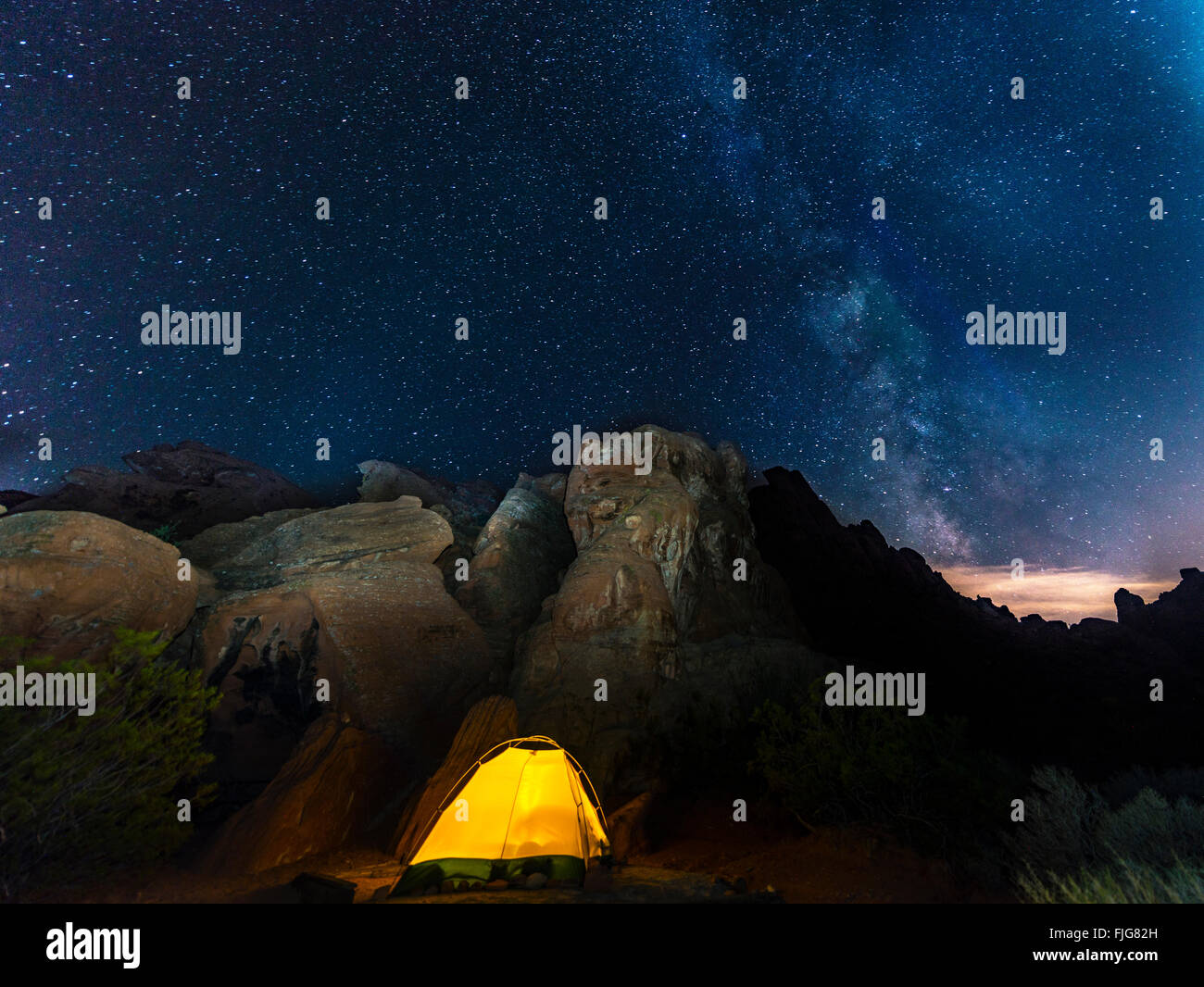Tent on a campsite with starry sky above and Milky Way, night scene, Wildrose Campground, Death Valley National - Stock Image
