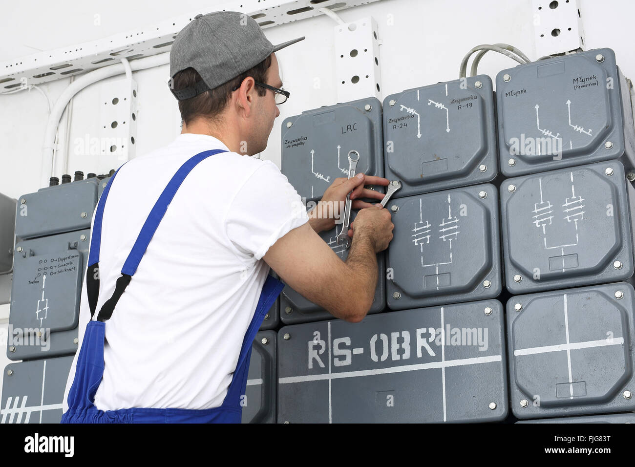 Electrician. Switching current home. Corks, electrical switches on the dashboard plugs. Electrician repairs dashboard. - Stock Image