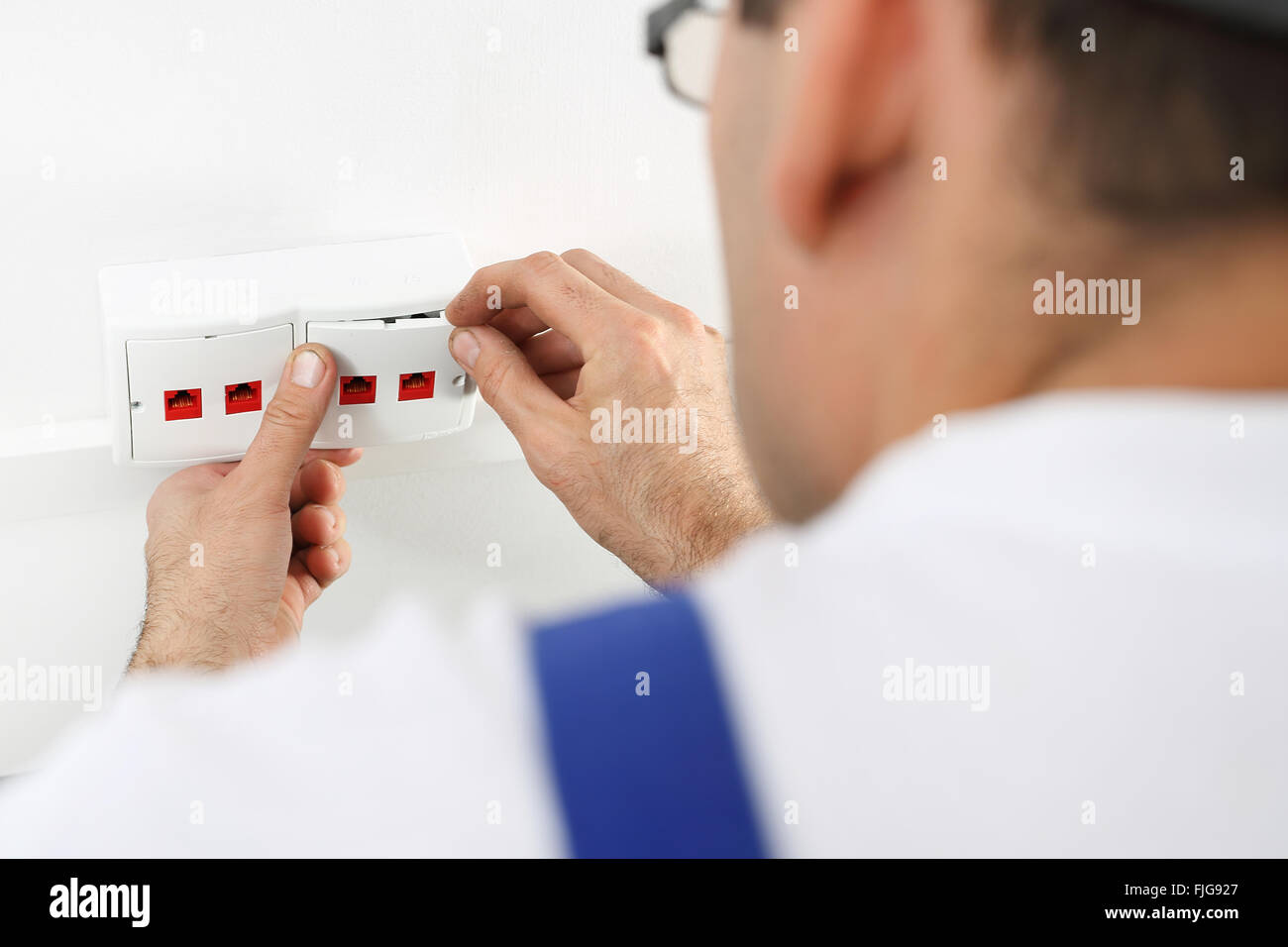 Electrician. Installing Internet. Installation of the wall socket. Man mounts in a wall electrical outlet, Internet - Stock Image