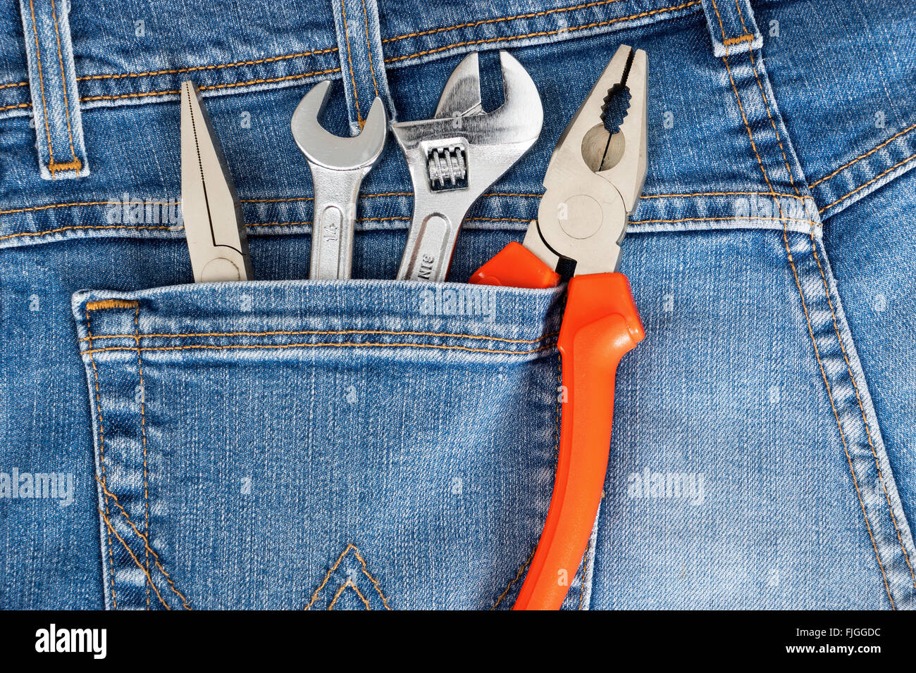 Toolkit of four items in a blue jeans pocket - Stock Image